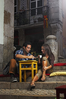 Portugal, Lisboa, Bairro Alto, young couple sitting at street cafe at dusk - BIF000004