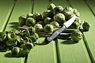 Brussel sprout on kitchen towel, knife on green wooden table - MAEF007398