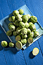 Brussel sprout on kitchen towel, knife on blue wooden table - MAEF007401