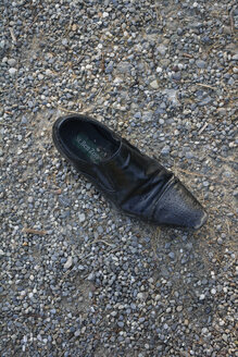Single black man's shoe at gravelly soil - AX000563
