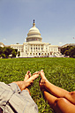 USA, Washington D.C., Couple relaxing in meadow in front of the Capitol - MBEF000902