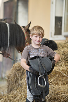 Germany, NRW, Korchenbroich, Boy holding saddle - CLPF000008