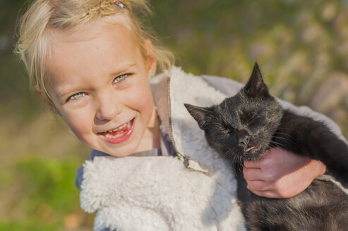 Portrait of little girl with cat in her arm, close-up - MJ000425