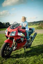 Germany, Saxony, little boy sitting on red motorcycle - MJ000422