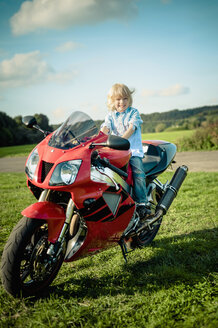 Germany, Saxony, little boy sitting on red motorcycle - MJ000422