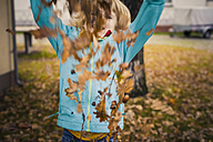 Little boy throwing autumn leaves - MJF000417