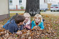 Three children lying at autumn foliage - MJF000414