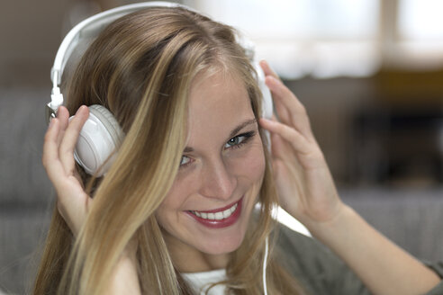 Portrait of smiling young woman with headphones, close-up - DR000303