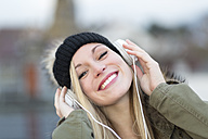Portrait of smiling young woman with headphones, close-up - DRF000297