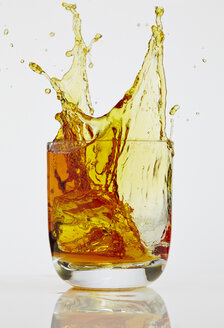 Ice cube splashing into glass of Whiskey - AKF000267
