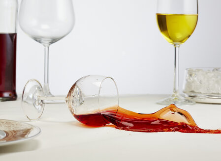 Glass of red wine toppling down on table - AKF000270