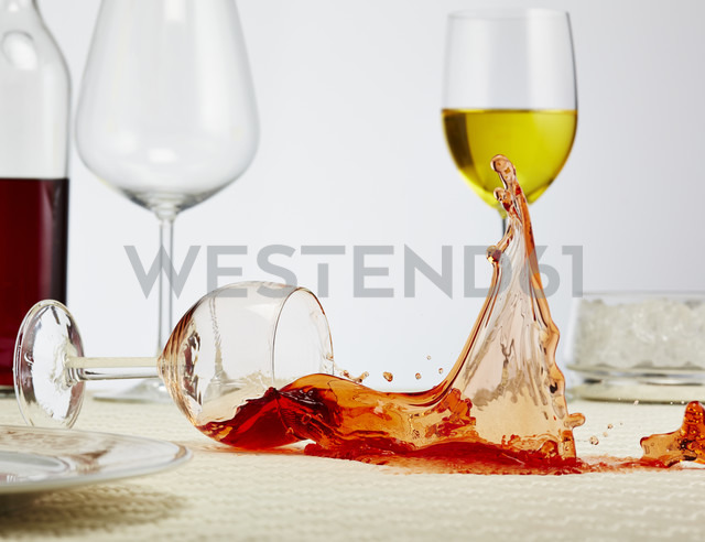 Glass of red wine toppling down on table - AKF000272