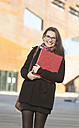 Smiling  student with folder outdoors, portrait - DISF000235