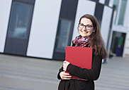 Smiling  student with folder outdoors, portrait - DISF000231