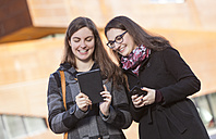 Two young women using digital tablet outdoors - DISF000227
