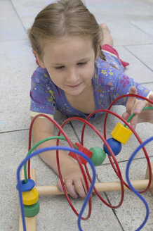 Little girl playing with coloured wooden toy - CRF002519
