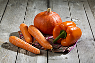 Hokkaido pumpkin, carrots and paprika on wooden table - MAEF007478