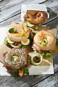 Four different bagels garnished with salami, sausage, slices of bacon, rocket salad, tomato, lettuce, cucumber carrot, egg, cream cheese and cress and parsley - MAEF007482