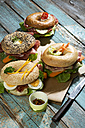 Four different bagels garnished with salami, slices of bacon, rocket salad, tomato, lettuce, cucumber carrot, egg, cream cheese and cress and parsley - MAEF007481