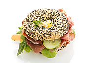 Poppy seed bagel garnished with slices of bacon, rocket salad, lettuce, cucumber, carrot, egg, cream cheese and cress - MAEF007491