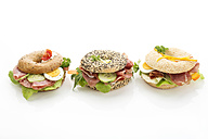 Three different bagels garnished with salami, slices of bacon, rocket salad, tomato, lettuce, cucumber carrot, egg, cream cheese and cress and parsley - MAEF007487