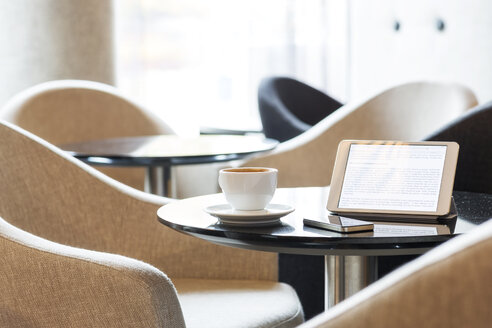 Digital tablet, smartphone and cup of coffee on table in hotel lobby - MLF000236