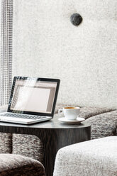 Poland, Warsaw, laptop and coffee cup at lounge of hotel - MLF000240