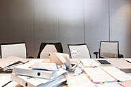 Poland, Warsaw, papers, mini tablet, laptops and folders on conference table at hotel - MLF000246
