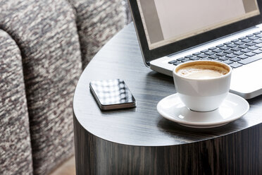 Poland, Warsaw, laptop, smartphone and coffee cup at lounge of hotel - MLF000247