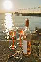Germany, Bavaria, Nonnenhorn, Bottle of wine and glasses on wall at shipping pier - SH001073