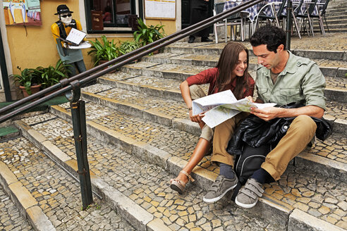 Portugal, Lisboa, Carmo, Calcada du Duque, young couple with city map sitting on stairs - BIF000077