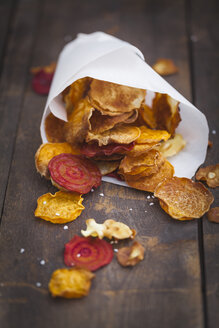 Roasted vegetable chips made of parsnips, sweet potatoes, beetroots, carrots and turnips on wooden table - ECF000396