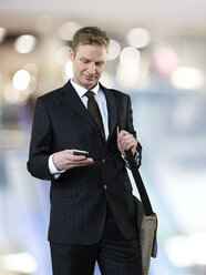 Businessman with sling bag using smart phone - STKF000703