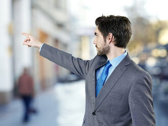 Young businessman pointing on something - STKF000713