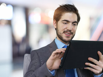 Portrait of businessman using tablet computer - STKF000709