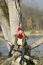 Young woman sitting at tree trunk - MAE007539