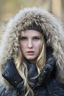 Portrait of young woman wearing hooded jacket - MAE007527