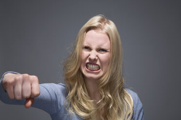 Portrait of furious young woman with outstretched fist and bared teeth - MAEF007521