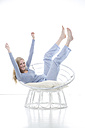 Blond young woman cheering in papasan chair - MAEF007549