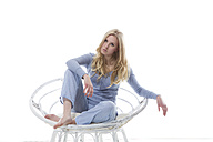 Blond young woman relaxing in papasan chair - MAEF007552