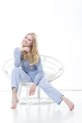 Blond young woman relaxing in papasan chair - MAEF007554