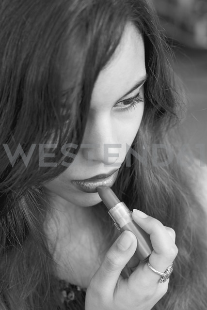 Young woman applying lipstick - DRF000313