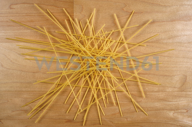 Raw spaghetti lying on wooden table - VI000150 - visual2020vision/Westend61