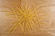 Raw spaghetti lying on wooden table - VI000150