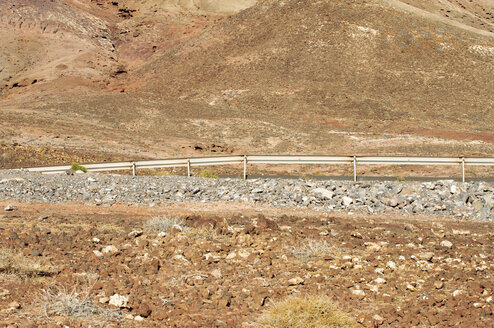 Spain, Fuerteventura, part of volcanic landscape with crash barrier - VI000089