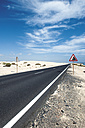 Spain, Fuerteventura, Corralejo, Parque Natural de Corralejo, view of empty road and road sign - VI000166