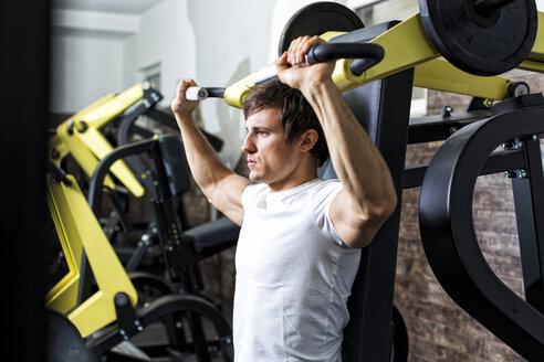 Austria, Klagenfurt, Man in fitness center doing machine workout - DAWF000055