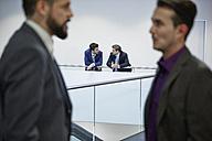 Germany, Neuss, Businessmen talking in corridor - STKF000799