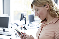 Gdermany, Neuss, Young woman in office using smart phone - STKF000808