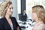 Germany, Neuss, Business people chatting in office - STKF000820